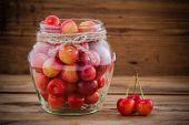 Rainier Cherries In Glass On Wooden Background