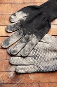 Dirty used fabric gloves on wooden background
