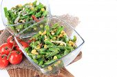 Salad with green beans, ham and  corn in glass bowls, on wooden board, isolated on white