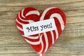 foto of miss you  - Miss you card with heart shaped lollipop on wooden surface - JPG