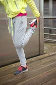Female Runner Stretching Leg Before Running