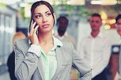 Thoughtful businesswoman talking on the smartphone in front of colleagues
