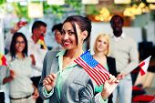 Happy businesswoman holding flag of USA in front of colleagues
