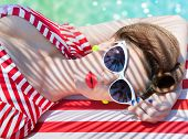 Colorful summer portrait of young attractive woman wearing sunglasses lying down by the swimming poo