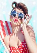stock photo of woman bikini  - Colorful summer portrait of young attractive woman wearing bikini and sunglasses sitting by the swimming pool - JPG