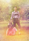 Loving couple in traditional Bavarian clothes posing together in countryside