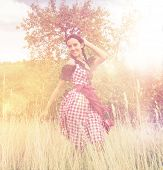 Young woman wearing a Bavarian dirndl posing in the field