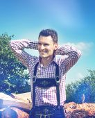 image of lederhosen  - Handsome guy wears a Lederhosen and poses outside in nature - JPG