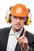 Businessman in black suit and safety hardhat helmet gesturing exclamation point finger sign white is