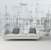 Greyscale image of an upholstered white sofa against an abstract wall with a grunge rustic pattern o