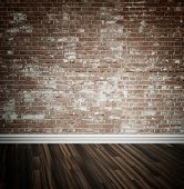 Rustic face brick interior wall and wooden parquet floor background with central highlight and skirt