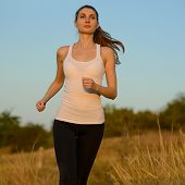 Young Beautiful Woman Running on the Mountain Trail in the Morning. Active Lifestyle