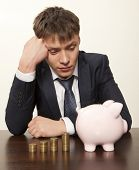 Frustrated businessman looking  pink piggy bank
