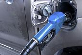 picture of vacuum pump  - Blue fuel nozzle in pouring to car - JPG