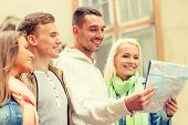 travel, vacation and friendship concept - group of smiling friends with city map exploring city