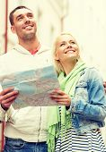 travel, vacation and friendship concept - happy couple with city map exploring city