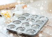 cooking, baking and home concept - close up of empty muffins molds and snow
