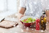 cooking, people, food, vegetarian and home concept - close of male hands holding bowl with salad in kitchen