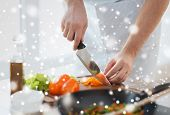 cooking, people, vegetarian food and home concept - close up of man chopping paprika and other vegetables on cutting board with big knife