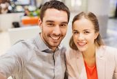 technology, photographing, and people concept - happy couple taking selfie with smartphone or camera in mall or office