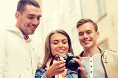 travel, vacation, technology and friendship concept - group of smiling friends with digital photocamera