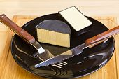 Cheddar cheese on black plate with fork and knife
