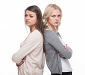 stock photo of not talking  - Unhappy young women are standing back each other and not speaking isolated on white background - JPG