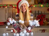 Portrait Of Happy Teenager Girl In Santa Hat Untangling Christma