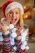 Portrait Of Happy Teenager Girl In Santa Hat Holding Tangled Christmas Lights