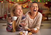 Portrait Of Laughing Girlfriends Having Christmas Snacks In Christmas Decorated Kitchen