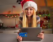Portrait Of Teenager Girl In Santa Hat With Credit Card And In Christmas Decorated Kitchen