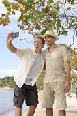 Vacation: Gay couple taking a selfie with mobile phone