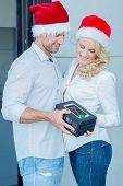 Couple Wearing Santa Hats Exchanging Unwrapped Christmas Gift of Tablet or Smartphone