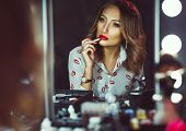 Beautiful Girl Doing Makeup With Red Lipstick