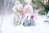 Happy family sitting in snow outdoor wintertime