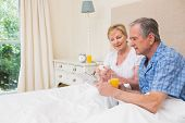 Senior couple having breakfast in bed at home in bedroom
