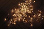 Christmas Lights Garland On Old Vintage Wooden Parquet Floor, Top View. Golden Lights.