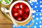 Traditional polish red borscht with dumplings and Christmas decorations on wooden background