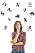stock photo of ordinary woman  - Ordinary casual beautiful woman surrounded with zodiac signs thoughtfully looking up with questionable face expression in jeans and shirt photo conception problems with horoscope good and bad sides and features - JPG