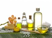 spa supplies with orchid, oil, yellow candle ,soap salt on banana leaf