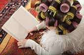 a girl with curlers reading a book, portrait