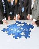 Meeting with people around a table with a puzzle with the words Social media