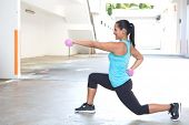 Beautiful hispanic sport woman doing lunges with two pink dumbbell, outdoor.