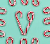 image of candy cane border  - Image of red and white stripped candy canes on a solid light green background - JPG