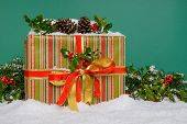 A gift wrapped Christmas present surrounded by a holly garland and snow, green background.