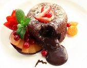 Hot chocolate pudding with fondant centre with fruits, close-up