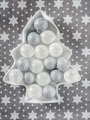 Christmas silver ball ornaments on white tree-shaped plate