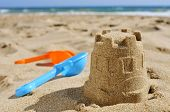 stock photo of shovel  - closeup of a sandcastle and toy shovels of different colors on the sand of a beach - JPG