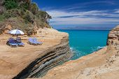 Beach Sunbeds And Umbrella On A Cliff Above The Blue Sea