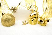 Golden Christmas Decoration On Snow With Wishes Card